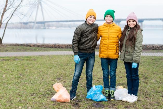 Long shot van schattige kinderen met plastic zakken