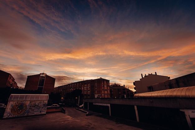 Long shot van talrijke gebouwen en huizen in de stad tijdens zonsondergang