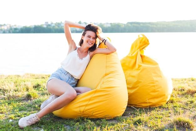 Long shot vrouw die zich voordeed op gele zitzak