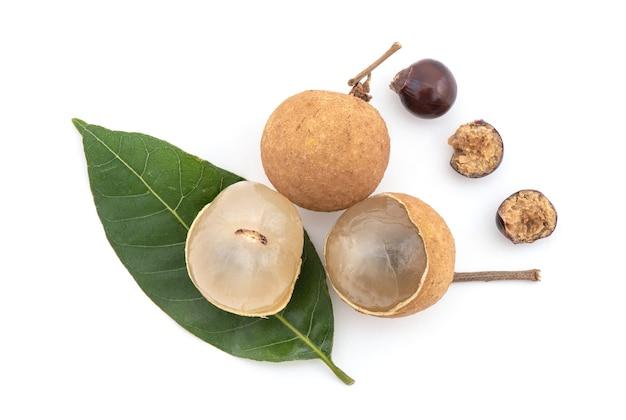 Longan of dimocarpus longan vruchten zaden en groen blad geïsoleerd op wit. bovenaanzicht, plat leggen.