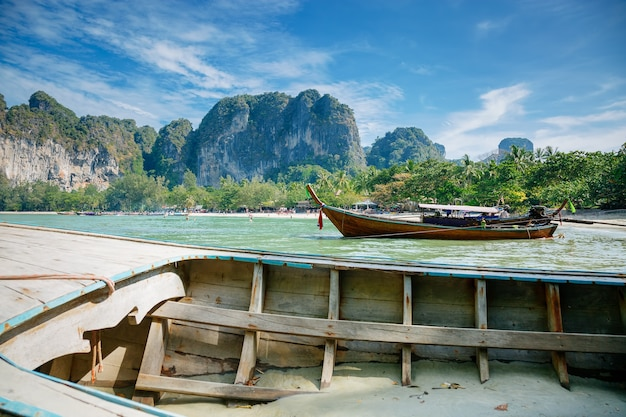 Longtailed boten o tropisch strand half ondergedompeld oude houten boot bergen en blauwe bewolkte hemel