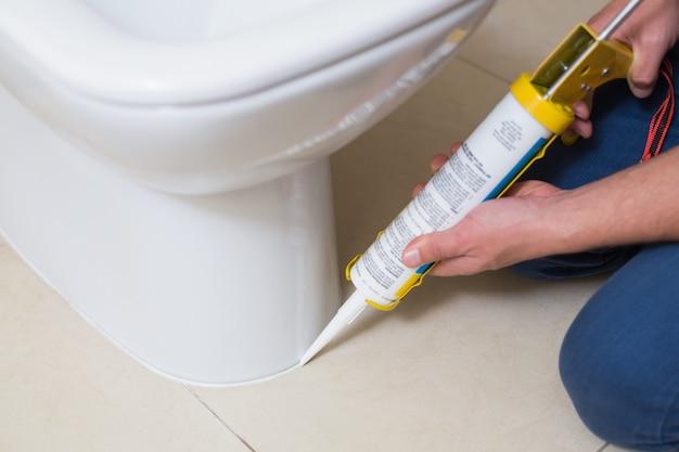 Loodgieter bevestigend toilet in een wasruimte met siliconecartridge