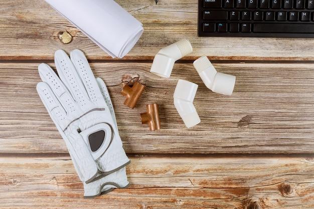 Loodgieter bouwer kantoor koperen leidingen en bouw blauwdrukken beschermende handschoenen computertoetsenbord
