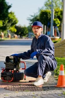 Loodgieter diagnosticeert een afvoerput op straat met behulp van speciale apparatuur.