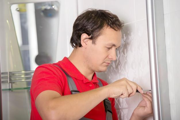 Loodgieter die een douche in slaapkamer herstelt.