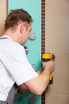 Loodgieter die een mixerkraan installeert in een badkamers