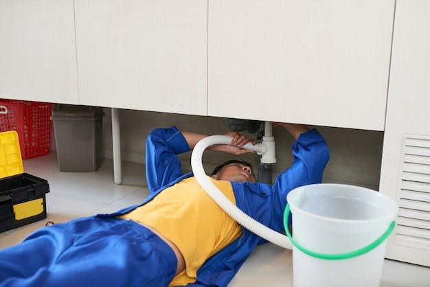 Loodgieter die gootsteenpijp bevestigt