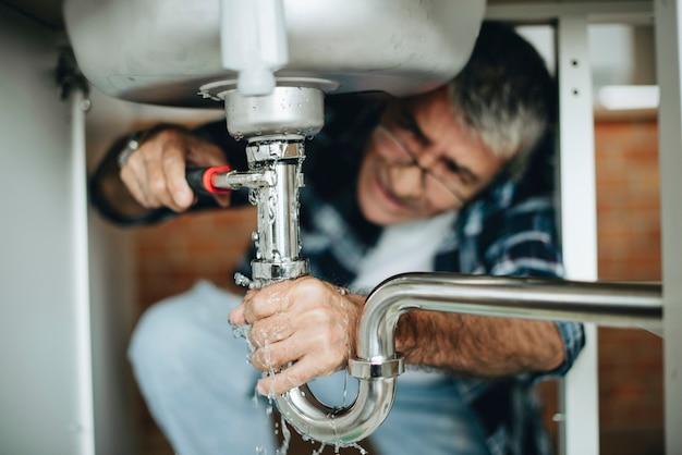 Loodgieter die het aanrecht bevestigt