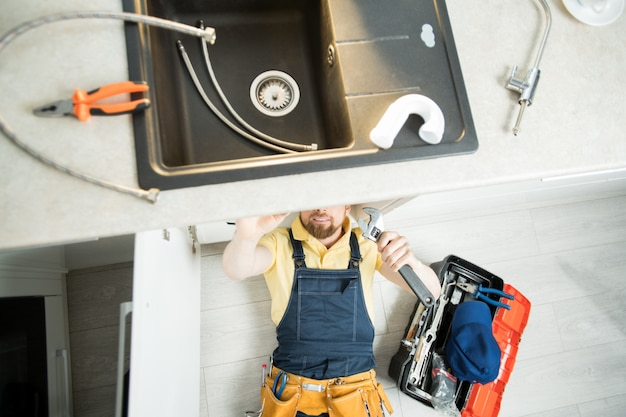 Loodgieter die pijp in keuken herstelt