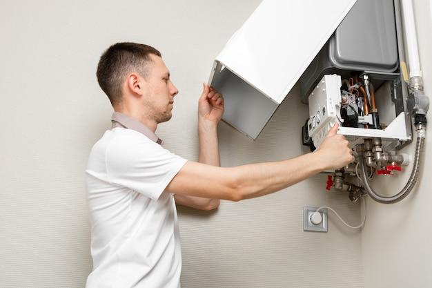 Loodgieter hecht een poging om het probleem met de residentiële verwarmingsapparatuur op te lossen. reparatie van een gasketel