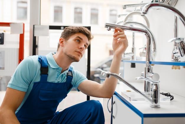 Loodgieter in uniform bij showcase in loodgieterswinkel. man met notebook die sanitaire techniek koopt in de winkel, waterkranen en kranenkeuze