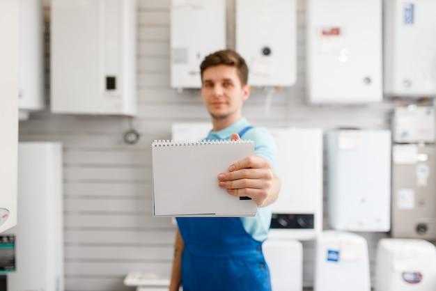 Loodgieter in uniform bij showcase met ketels in loodgieterswinkel. man met notebook die sanitaire techniek koopt in de winkel, waterkranen en kranenkeuze