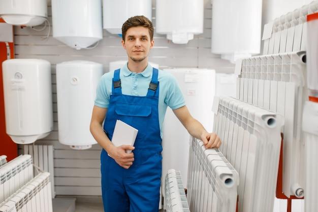 Loodgieter in uniform die waterverwarmingsradiator kiest bij showcase in loodgieterswinkel. man koopt sanitaire techniek in winkel