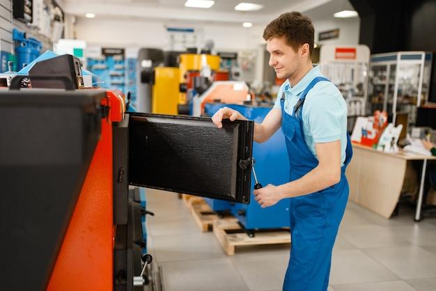 Loodgieter in uniform kiezen ketel met oven bij showcase in loodgieterswinkel. man met notebook die sanitaire techniek in de winkel koopt, waterverwarmerkeuze