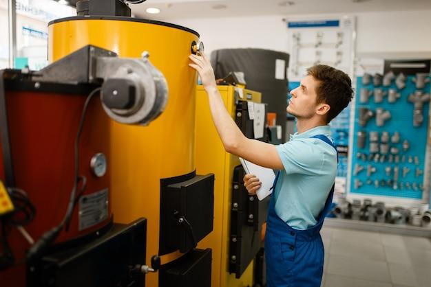 Loodgieter in uniforme koopketel met oven bij showcase in loodgieterswinkel. man met notebook die sanitaire techniek in de winkel koopt, waterverwarmerkeuze