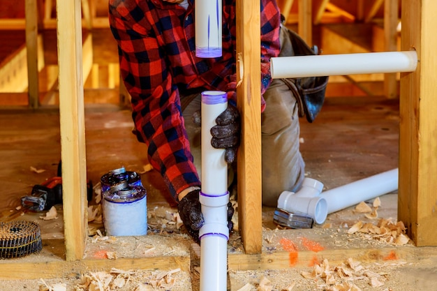 Loodgieter lijm witte pvc-buis, een nieuwe plastic afvoer monteren op nieuw huis