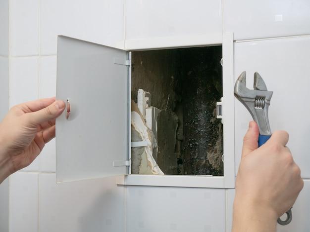 Loodgieter met moersleutel open kleine deuropening naar pijpen