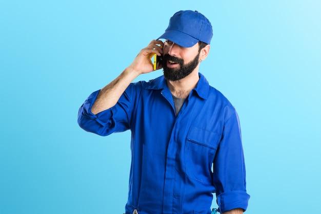 Loodgieter praten met mobiele op kleurrijke achtergrond