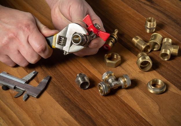 Loodgieter schroeft de koperen fitting op de klep met een sanitaire sleutel. handen van de meester close-up