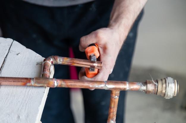 Loodgieter van de de loodgietersarbeider van de close-up snijdt de professionele pijp en houdt het met buigtang.