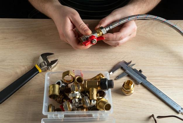 Loodgieter verbindt messing fittingen en slang tijdens het repareren van apparatuur. close-up van de hand van de meester tijdens het werk