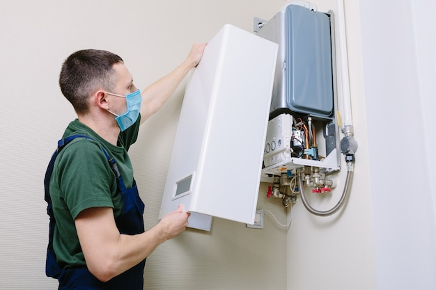 Loodgieter werkt mee en probeert het probleem met de verwarmingsapparatuur voor woningen op te lossen. reparatie van een gasboiler