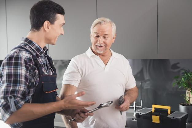 Loodgieters houden een sleutel in handen