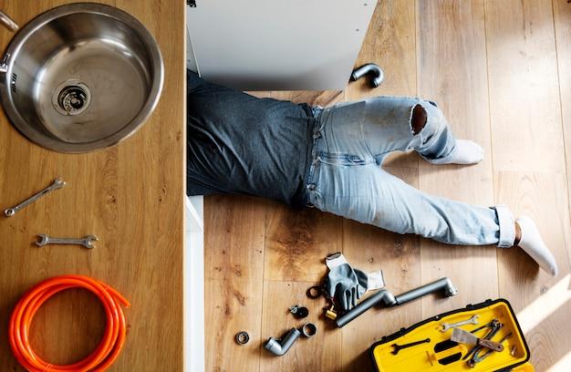 Loodgietersmens die keukengootsteen bevestigen