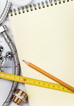 Loodgieterswerk en hulpmiddelen met een notitieboekje