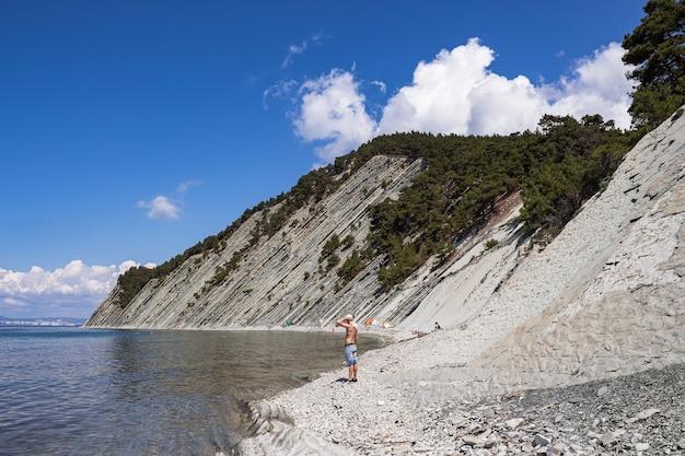 Loop langs het stenen wilde strand aan de voet van de kliffen.