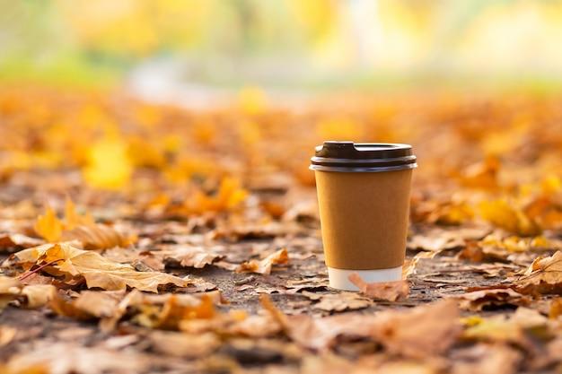 Loop met een kop warme chocolademelk in het herfstpark. ambachtelijke kop koffie op de weg met gele gevallen bladeren.