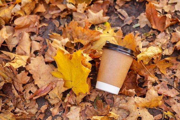 Loop met een kopje warme chocolademelk in het herfstpark. ambachtelijke kopje koffie op de weg met gele gevallen bladeren