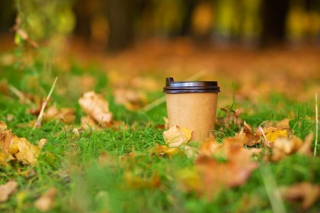 Loop met een kopje warme chocolademelk in het herfstpark. ambachtelijke kopje koffie op het gras met gele gevallen bladeren