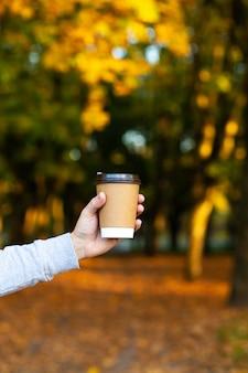 Loop met een kopje warme chocolademelk in het herfstpark.