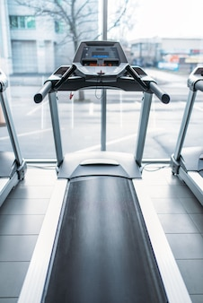 Loopband tegen groot raam, sportschool interieur, niemand, joggingbaan, stationaire hardloopsimulator, sportuitrusting in fitnessclub