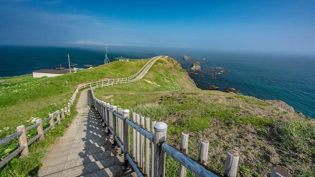 Loopbrug houten hek met uitzicht op zee punt blauwe hemelachtergrond