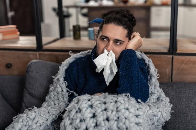 Loopneus. trieste zieke man zittend op de bank met papieren zakdoekjes in zijn neus