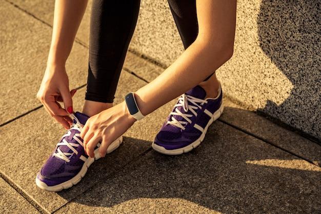 Loopschoenen. barefoot hardloopschoenen close-up. vrouwelijke atleet die veters bindt om op de weg te joggen in minimalistische hardloopschoenen op blote voeten. loper maakt zich klaar voor training. sportieve levensstijl. Premium Foto