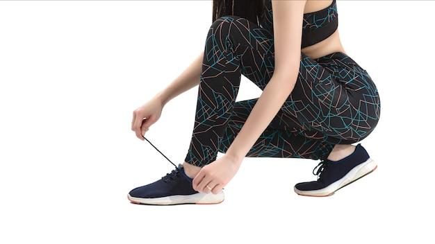 Loopschoenen close-up. vrouwelijke atleten binden schoenen om zich voor te bereiden op het uitoefenen van een afgelegen witte achtergrond. loper maakt zich klaar voor training. sportieve levensstijl.