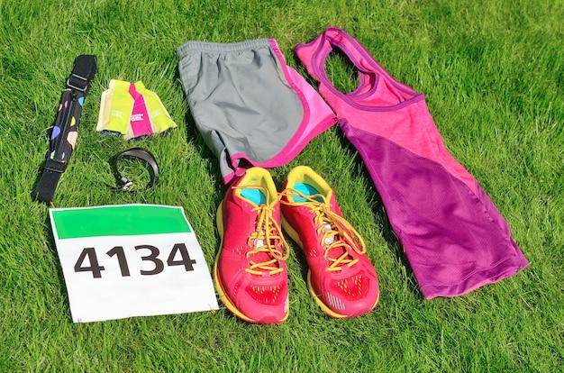 Loopschoenen, marathon race-slab (aantal), hardloopuitrusting en energiegels op gras, sportcompetitie, fitness en een gezond levensstijlconcept