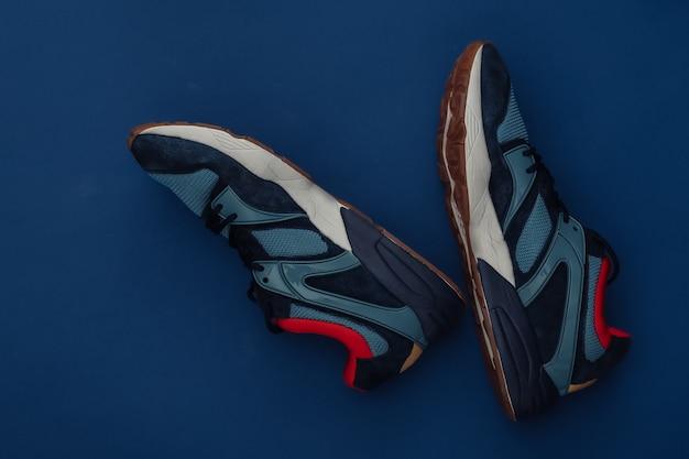 Loopschoenen (sneakers) op klassieke blauwe achtergrond. gezonde levensstijl, fitnesstraining. kleur 2020. bovenaanzicht