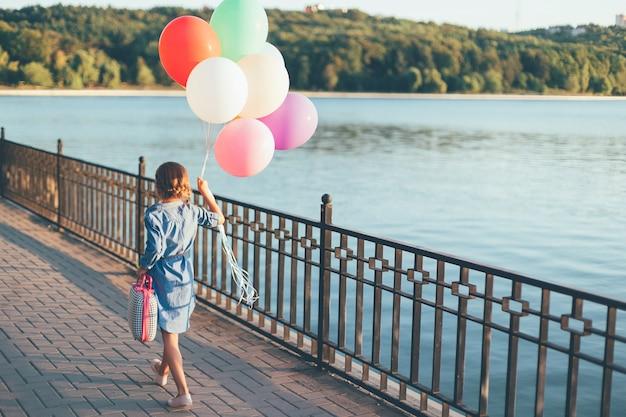 Lopend meisje die kleurrijke ballons en kinderachtige koffer houden