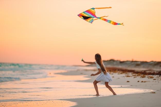 Lopend meisje met vliegende vlieger op tropisch strand. kid spelen op oceaan kust.