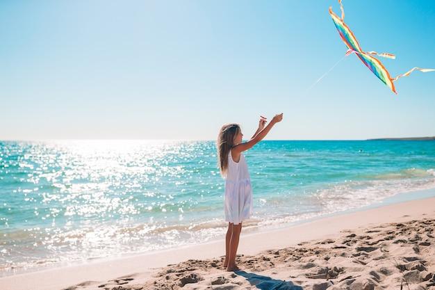 Lopend meisje met vliegende vlieger op tropisch strand