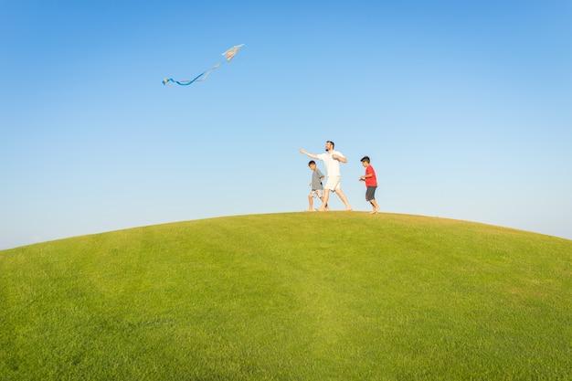 Lopend met vlieger op de vakantie van de de zomervakantie, perfecte weide en hemel op kust