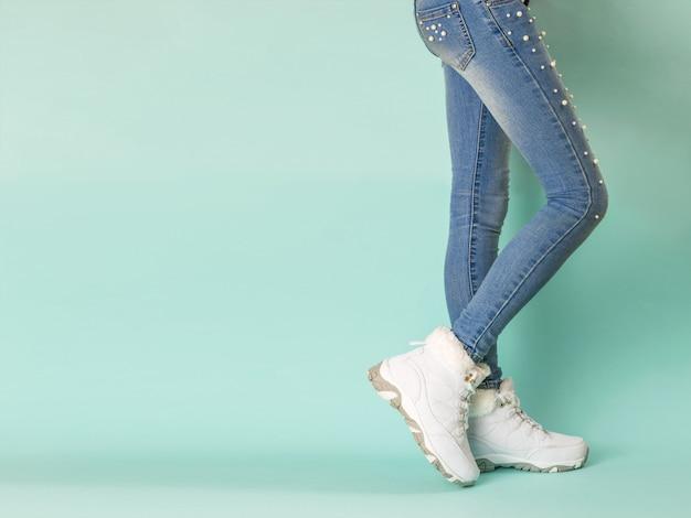 Lopende benen van een meisje in strakke jeans op blauw. wintersportstijl.