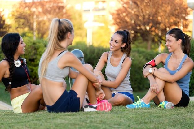 Lopende meisjes met plezier in het park met mobiele telefoon.
