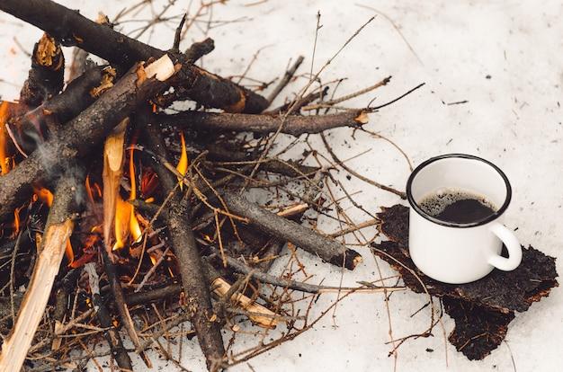 Lopende mok met koffie dichtbij het kampvuur. concept wandeling, wandeling, reis in de winter