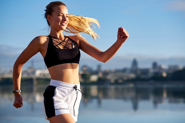 Lopende vrouw bij zonsopgang. ochtend joggen op het strand of de kust van de rivier op de achtergrond van de stedelijke stad