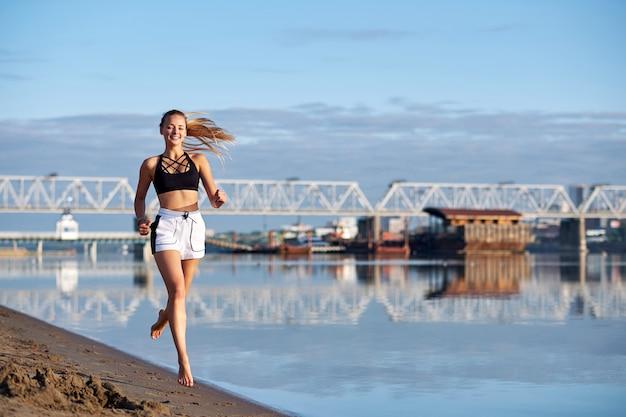 Lopende vrouw in het zand bij zonsopgang. ochtend joggen op blote voeten op het strand of de kust van de rivier op stedelijke stad achtergrond